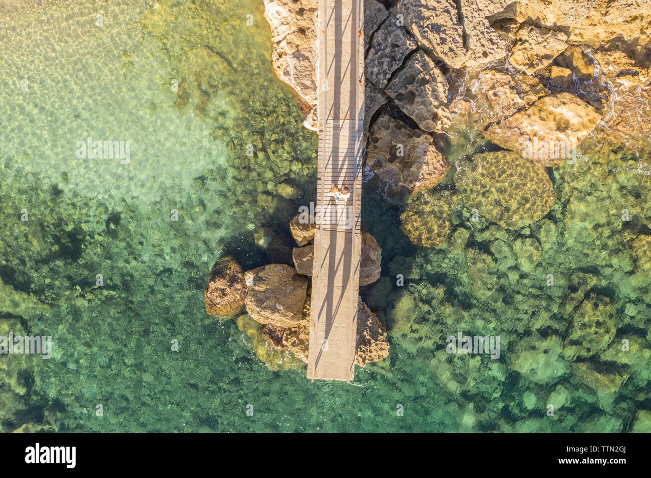 Drone view of female friends walking on pier over sea during sunny day - Stock Image