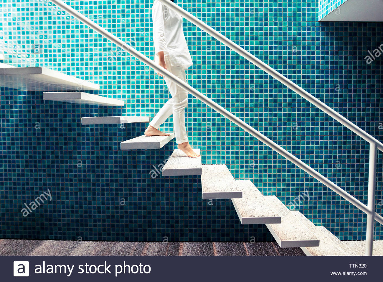 Low section of woman moving down floating steps at home - Stock Image