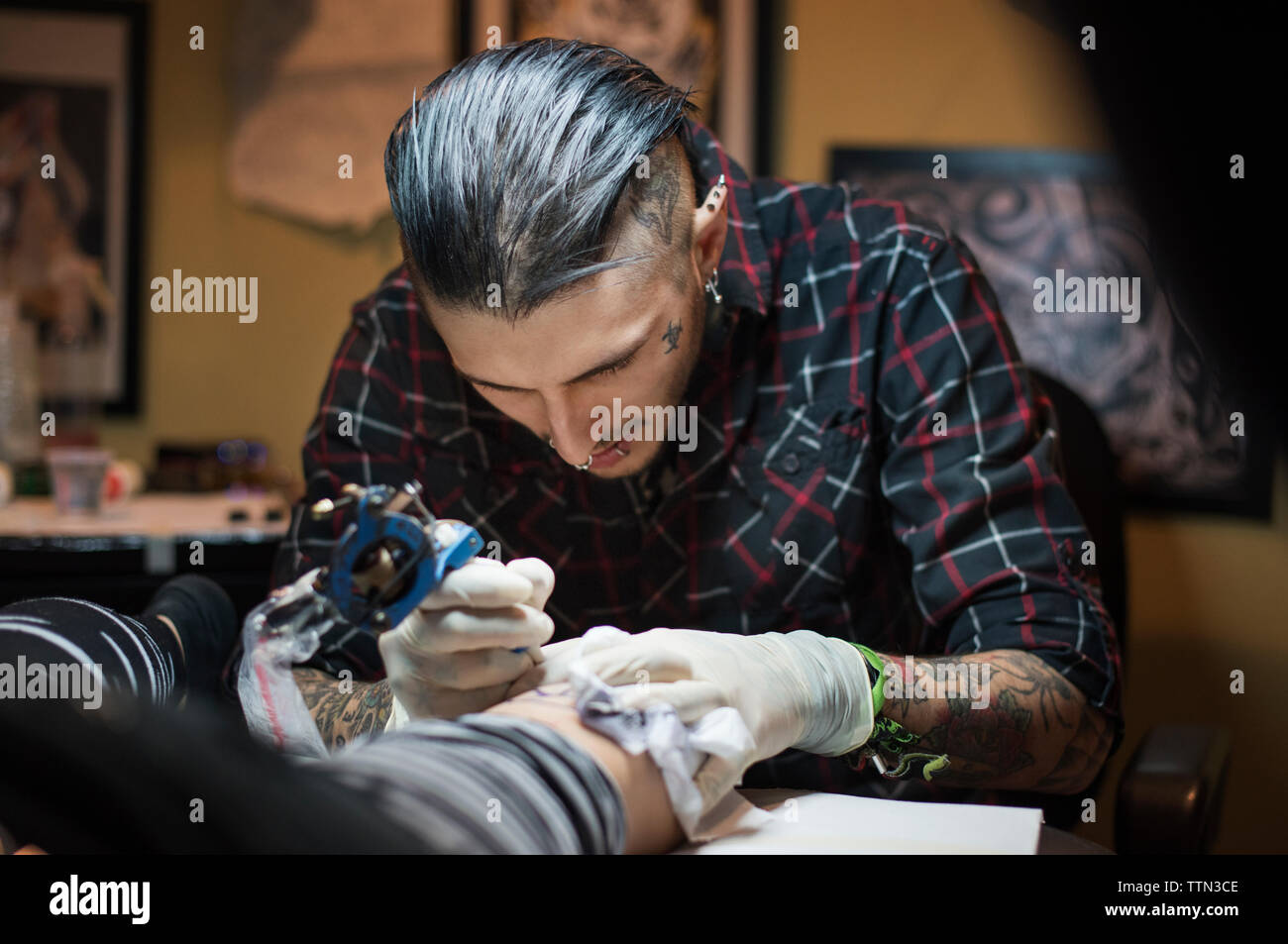 Male tattoo artist tattooing female client in studio - Stock Image