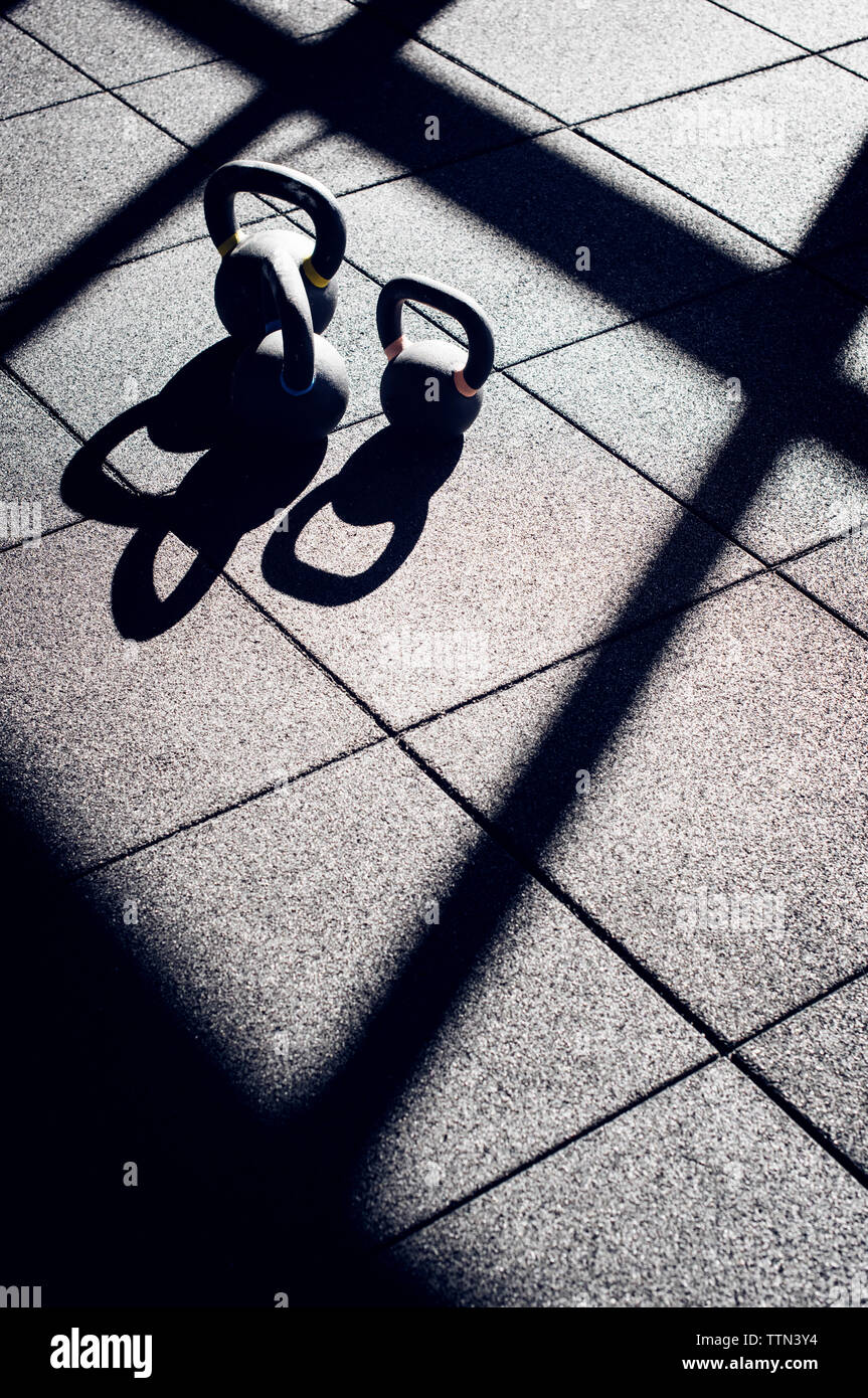 High angle view of kettlebells on tiled floor in gym - Stock Image