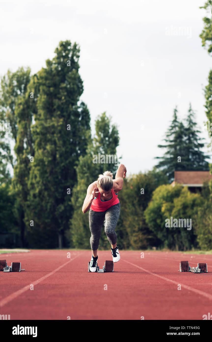 Athlete running from starting block on track Stock Photo