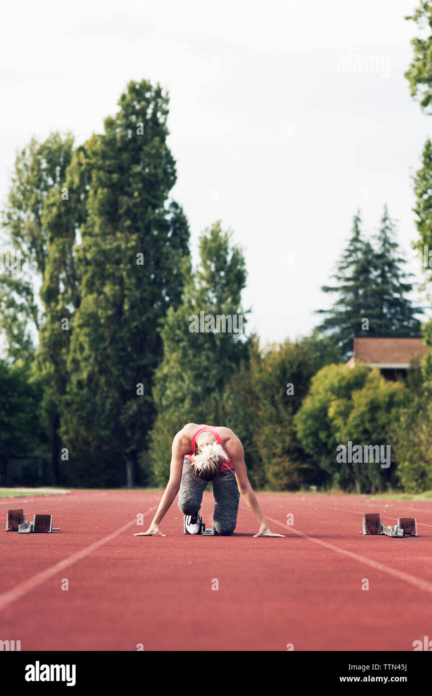 Athlete poised at starting block on track - Stock Image