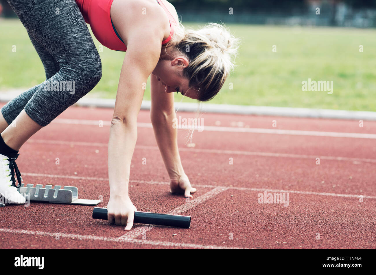 Athlete with relay baton poised at starting block on track Stock Photo