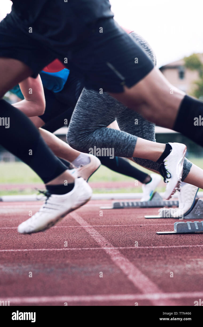 Athletes sprinting from starting blocks on track Stock Photo