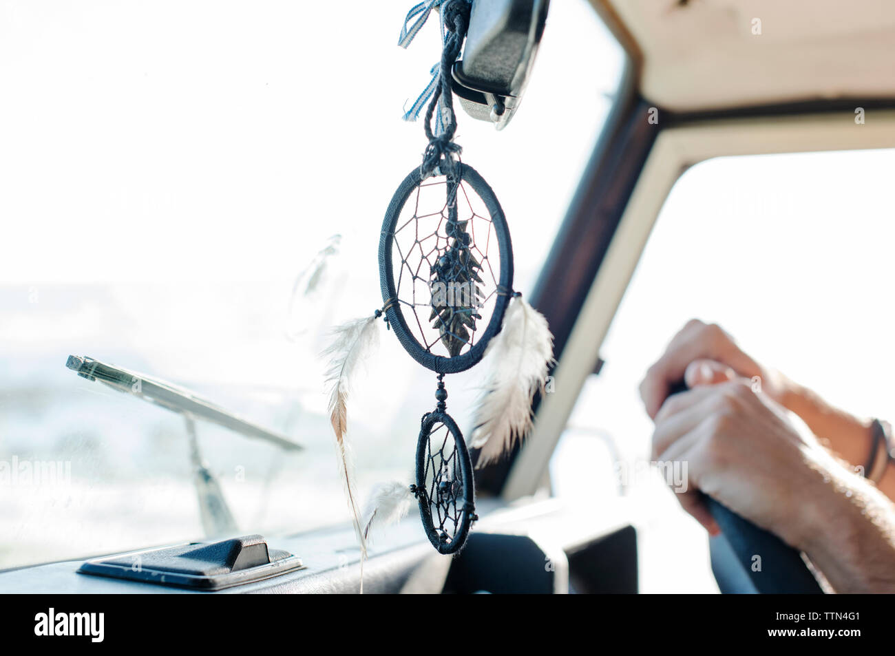 Cropped hands of man by dreamcatcher driving off-road vehicle - Stock Image