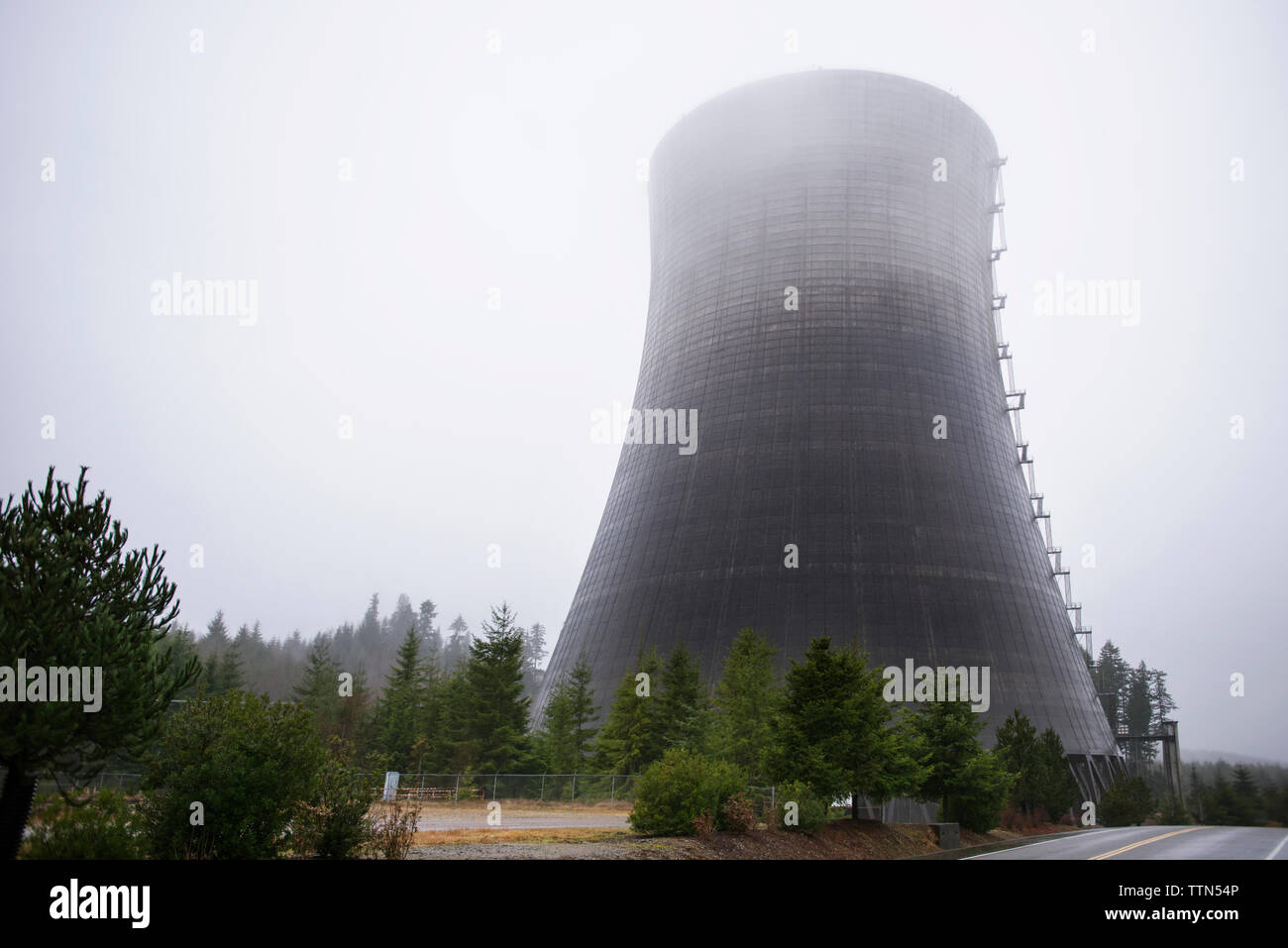 Low angle view of nuclear reactor in foggy weather against sky - Stock Image