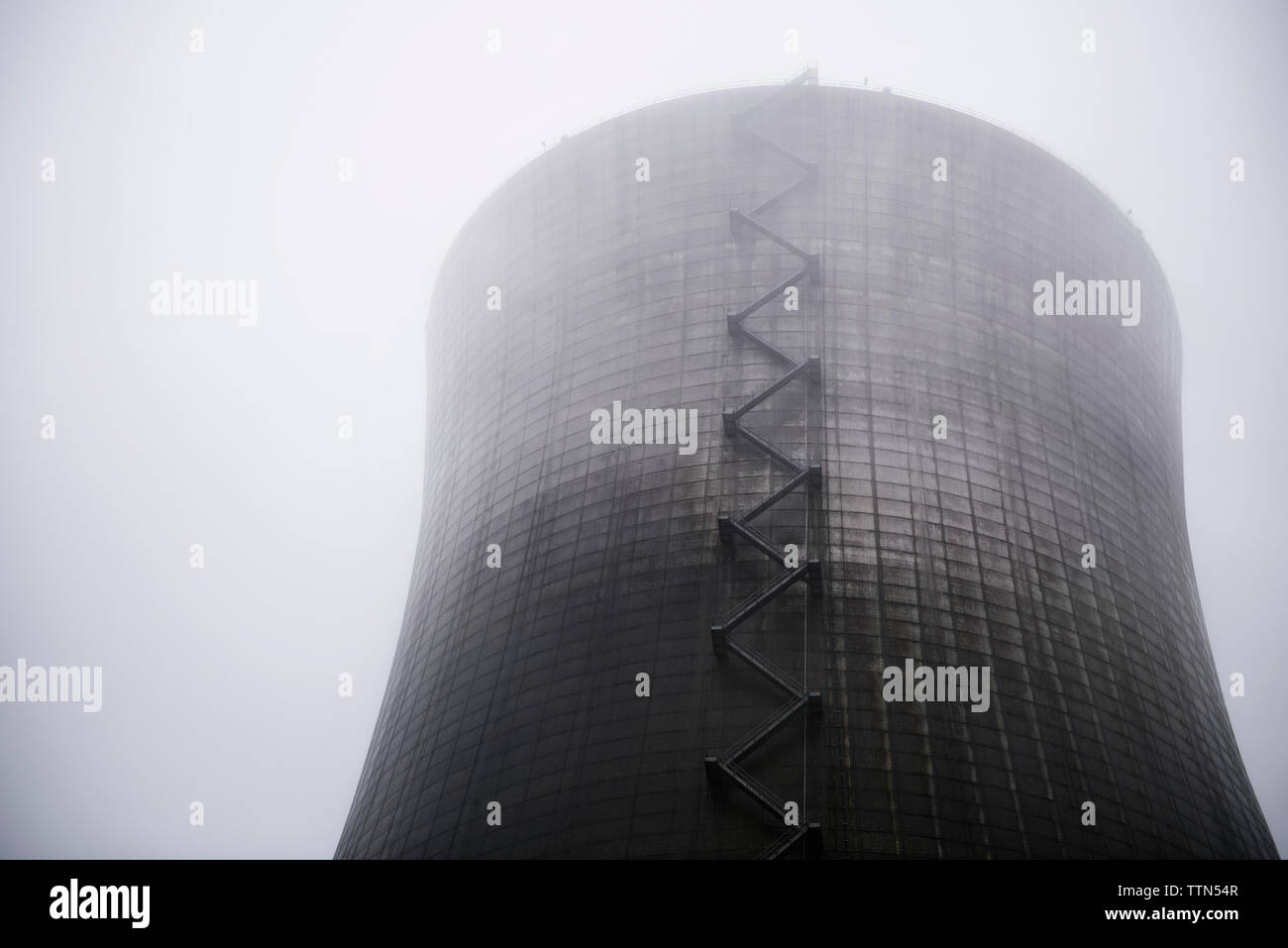Low angle view of nuclear reactor in foggy weather - Stock Image