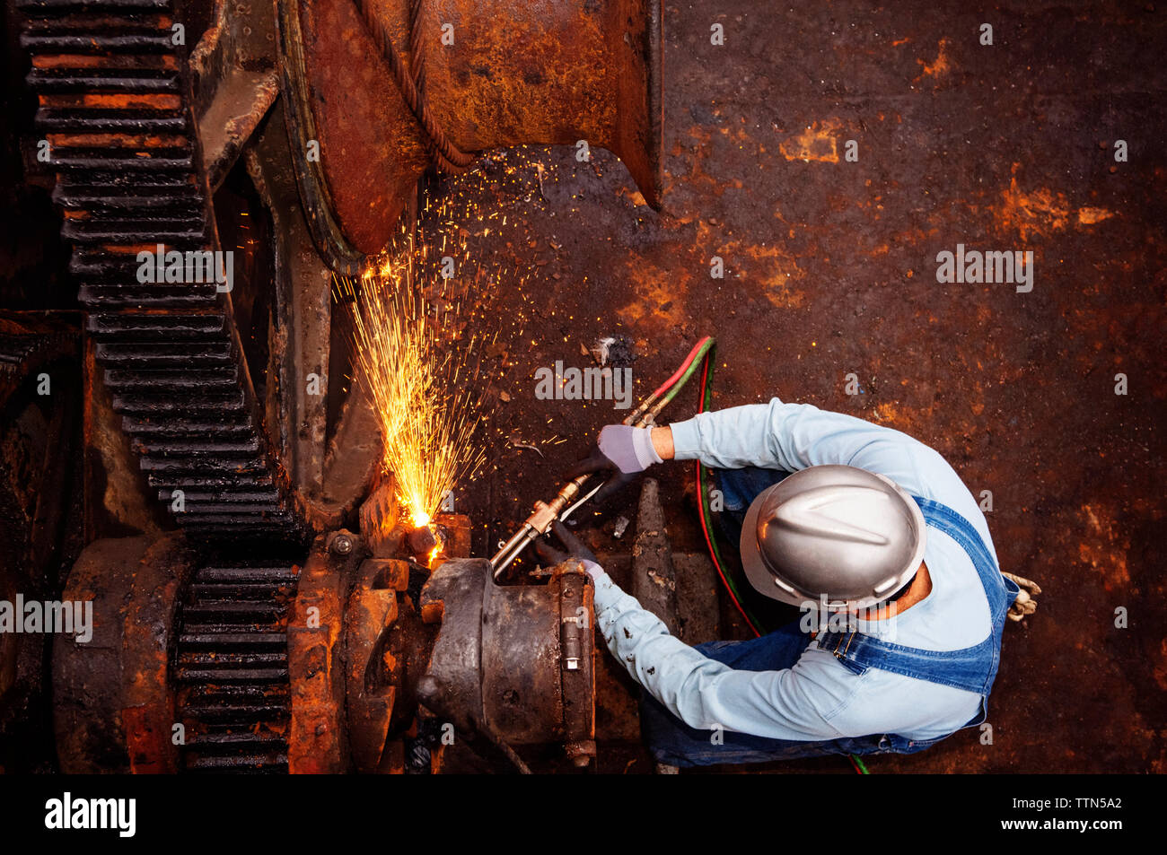 Overhead view of worker welding machinery at industry Stock Photo