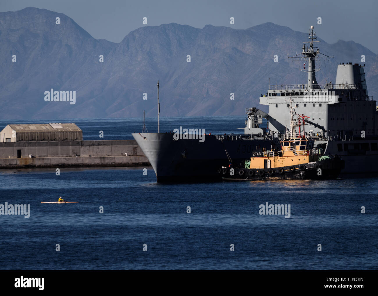 The SAS Drakensberg fleet replenishment ship at the Simons Town naval base in the Western Cape, South Africa, with a man skulling - Stock Image