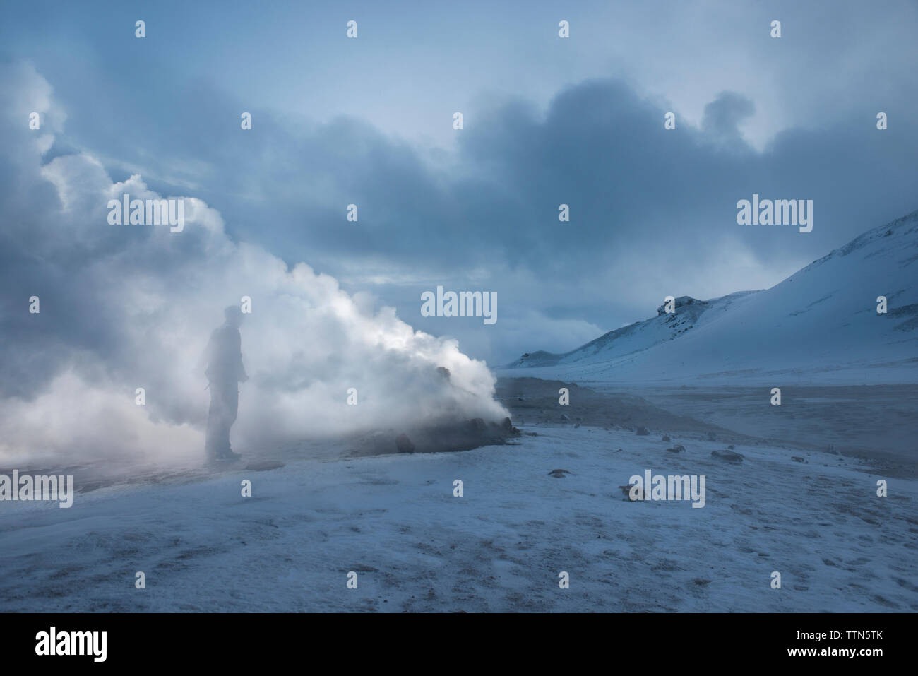 Man standing by fumaroles emitting steam on snow covered field - Stock Image