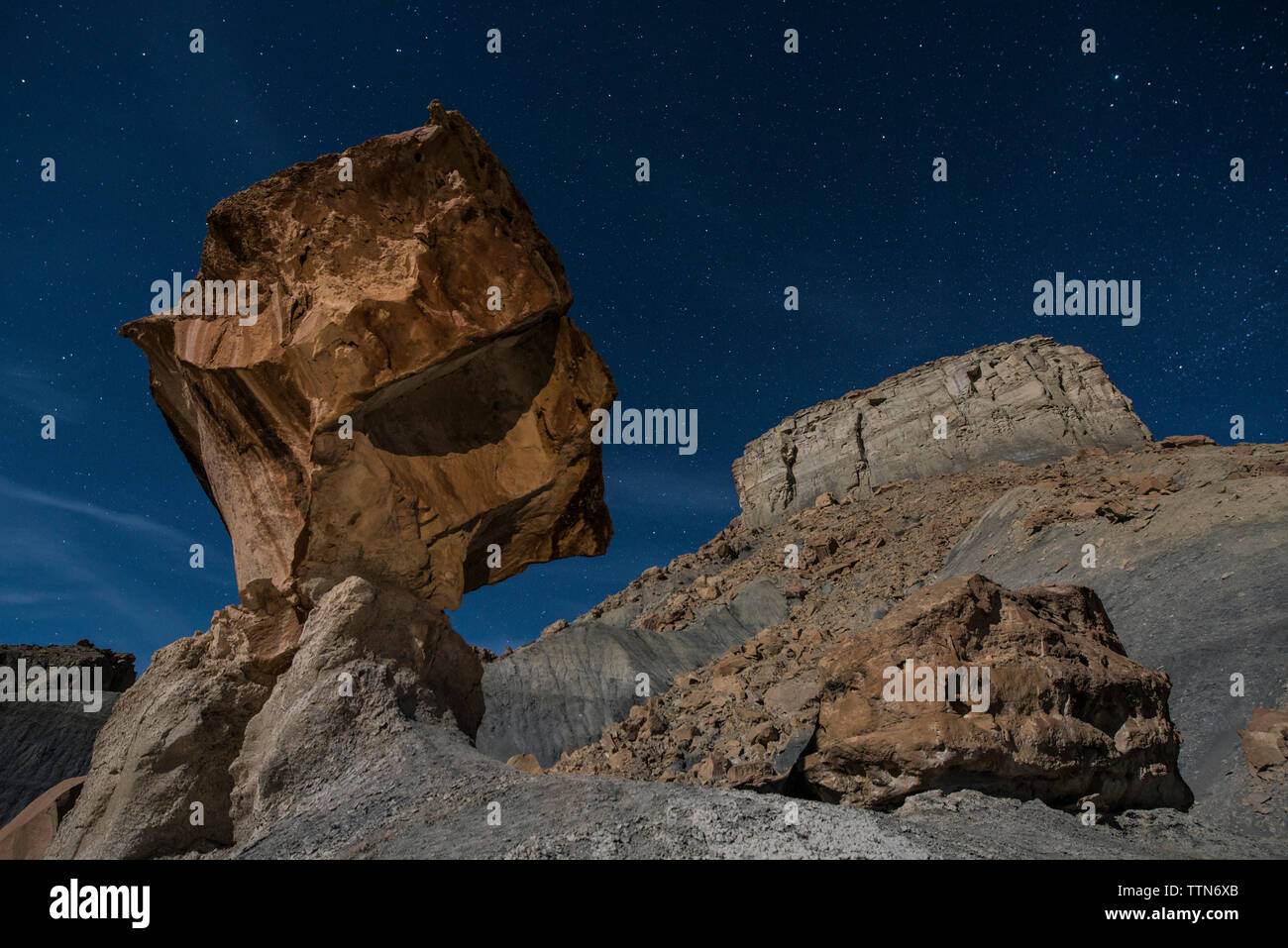 Low angle view of rock formations against star field at Grand Staircase-Escalante National Monument Stock Photo