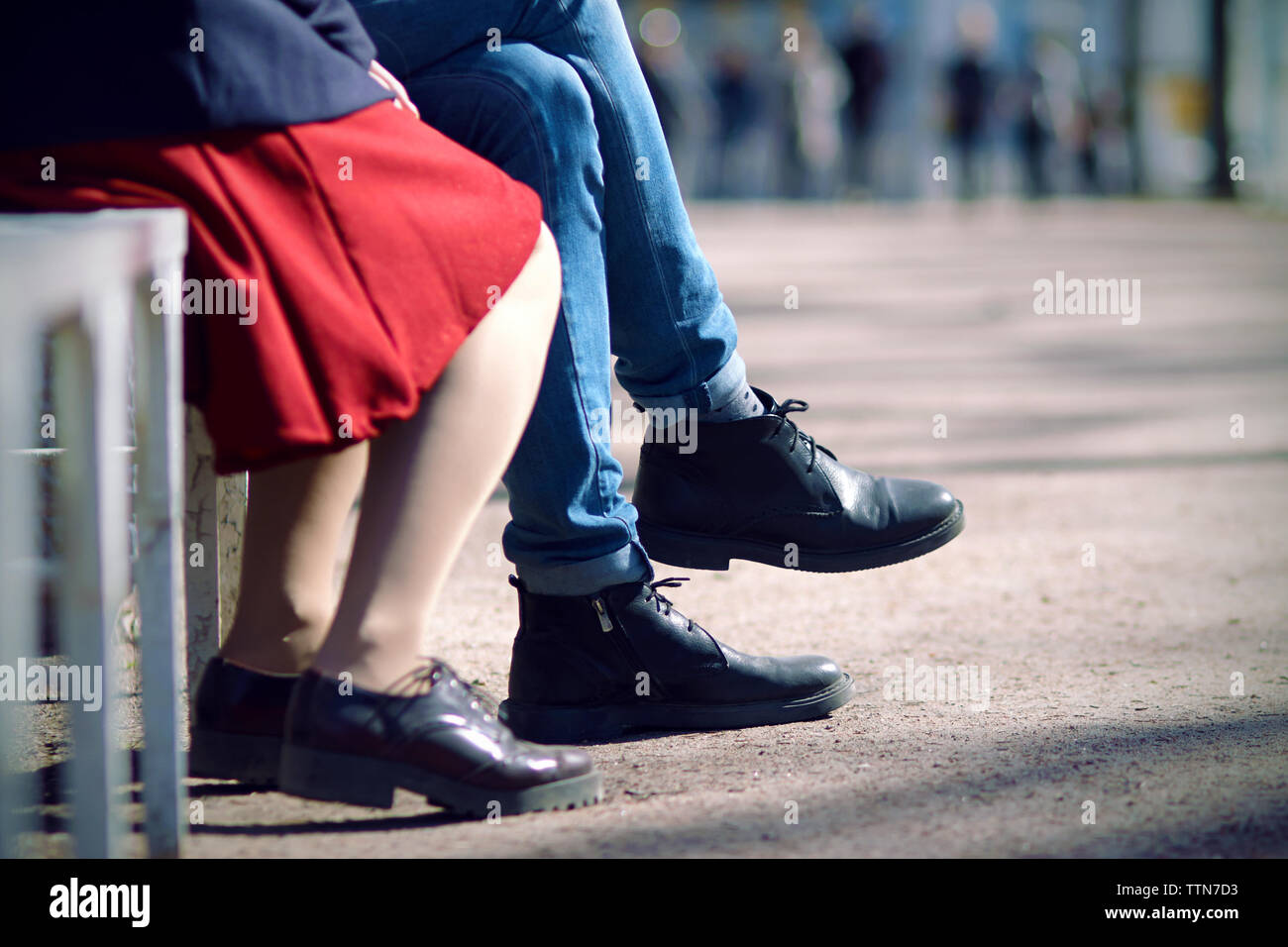 59359e44c Legs of a young couple sitting on a summer day on a bench. The man
