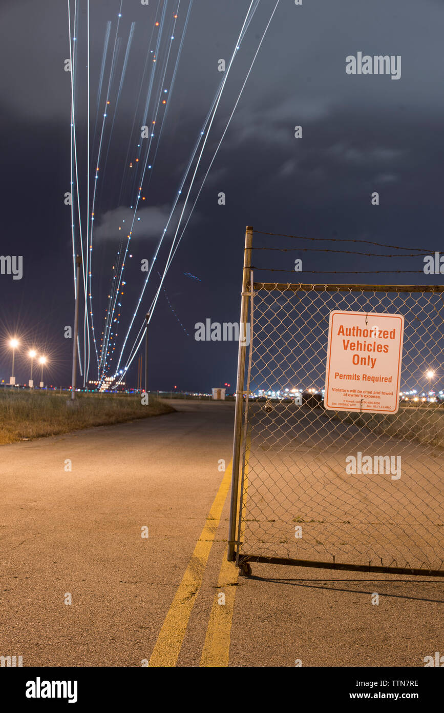 Low angle view of light paintings over road against cloudy sky at night Stock Photo