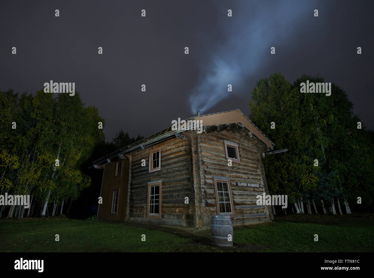Smoke emitting from chimney on Slaven's roadhouse by trees at Yukon Charley Rivers National Preserve against sky at night Stock Photo