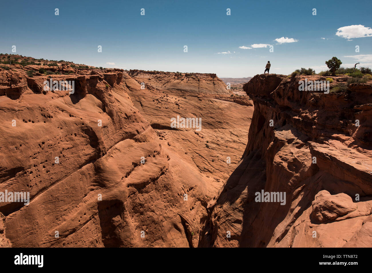 Mid distance view of man standing on cliff at Grand Staircase-Escalante National Monument against sky Stock Photo