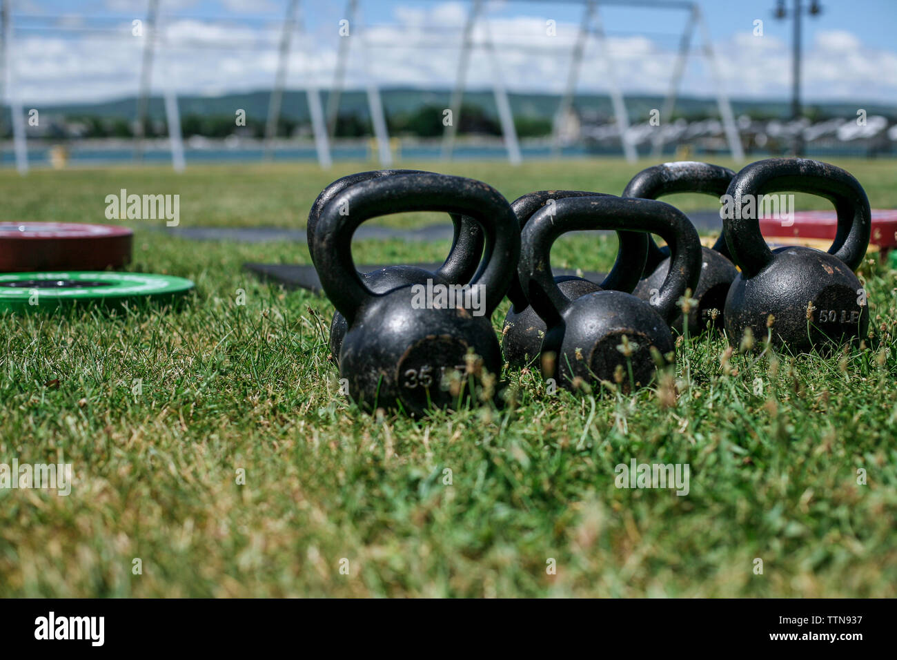 Close-up of kettlebells on grassy field at park during sunny day - Stock Image