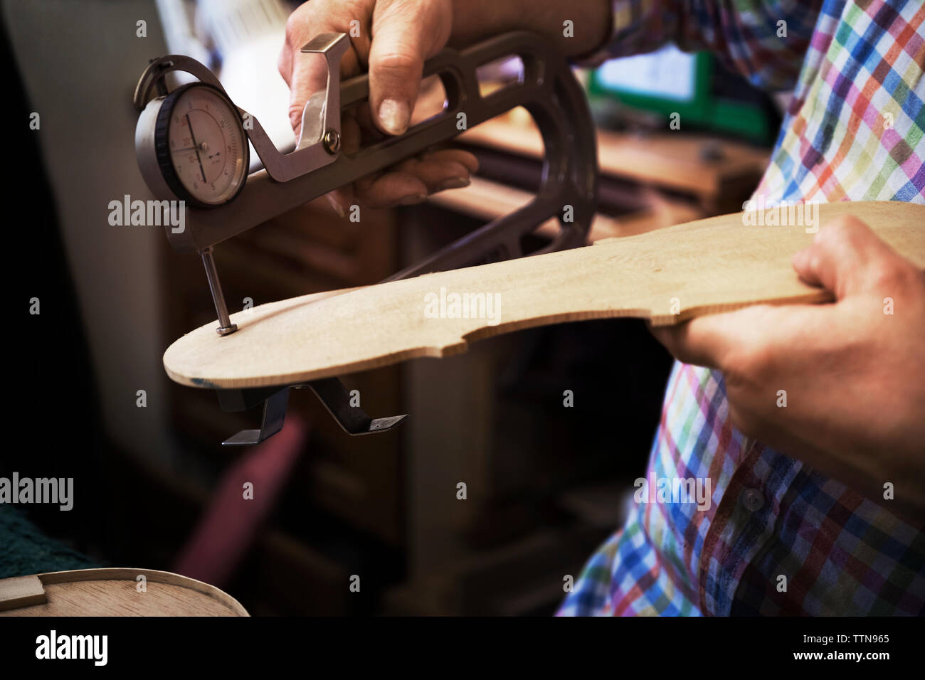 Midsection of craftsman using hand tool to measure wood at workshop - Stock Image