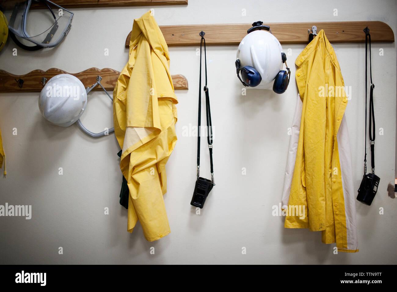 Protective workwear hanging from coat hooks - Stock Image