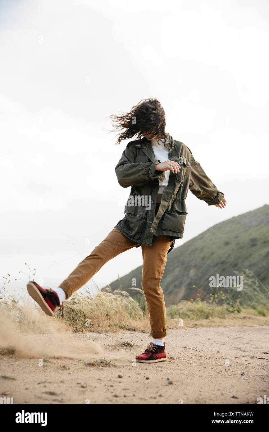 Woman with tousled hair dancing on sand against clear sky - Stock Image