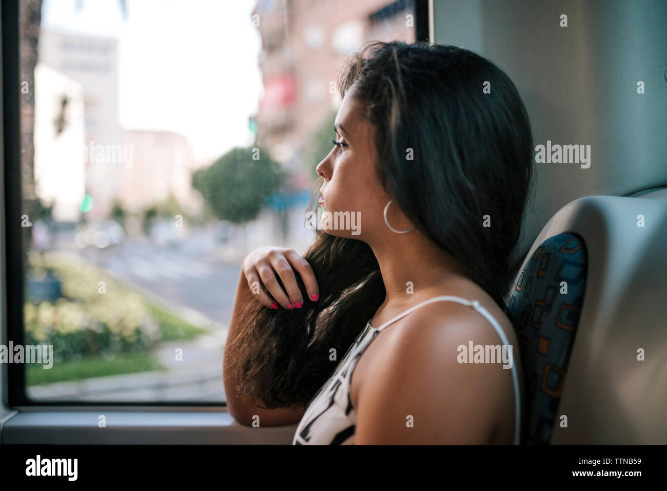Side view of thoughtful serious woman looking through window while sitting in bus - Stock Image