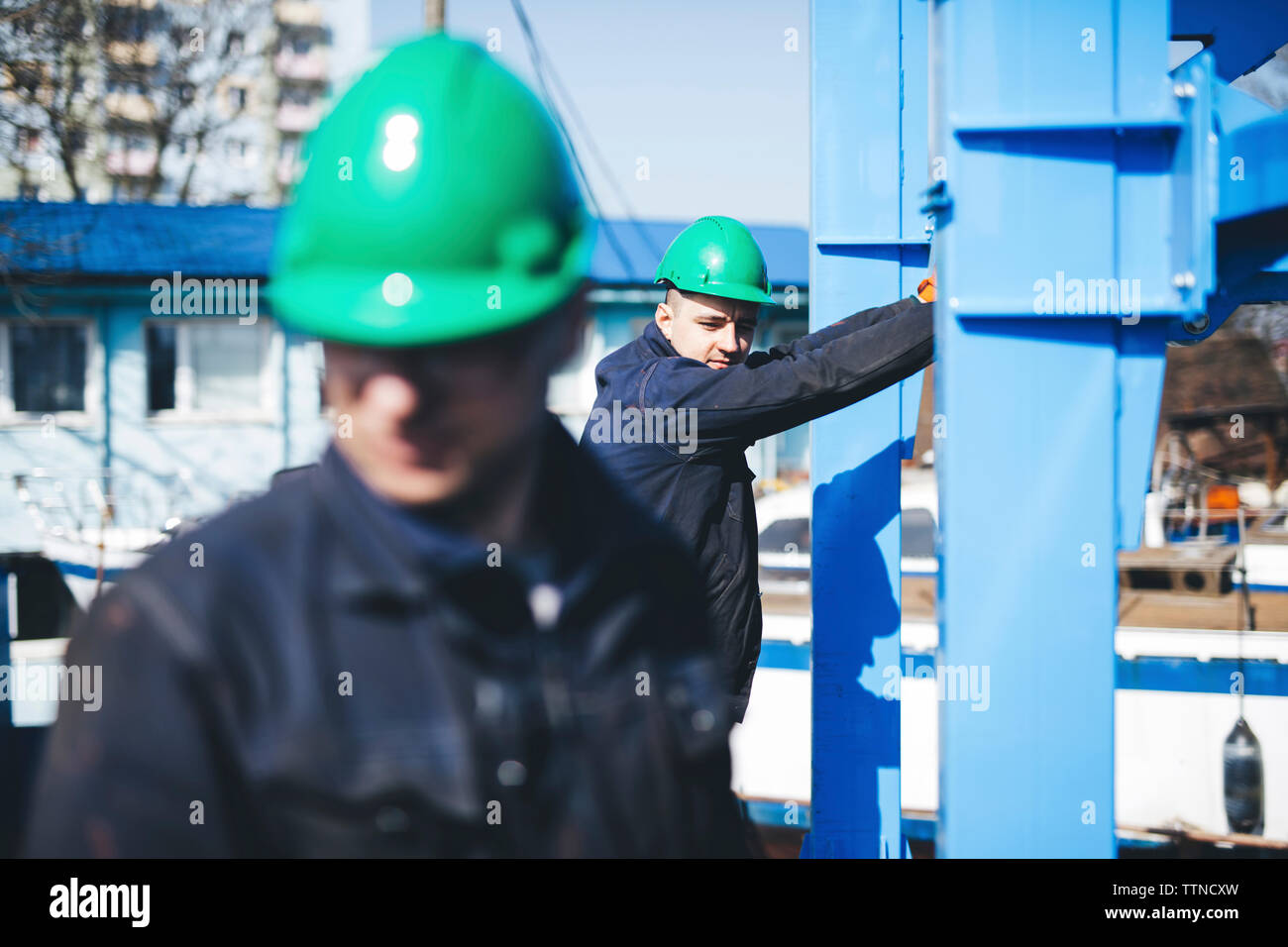 Manual workers working at shipyard during sunny day - Stock Image