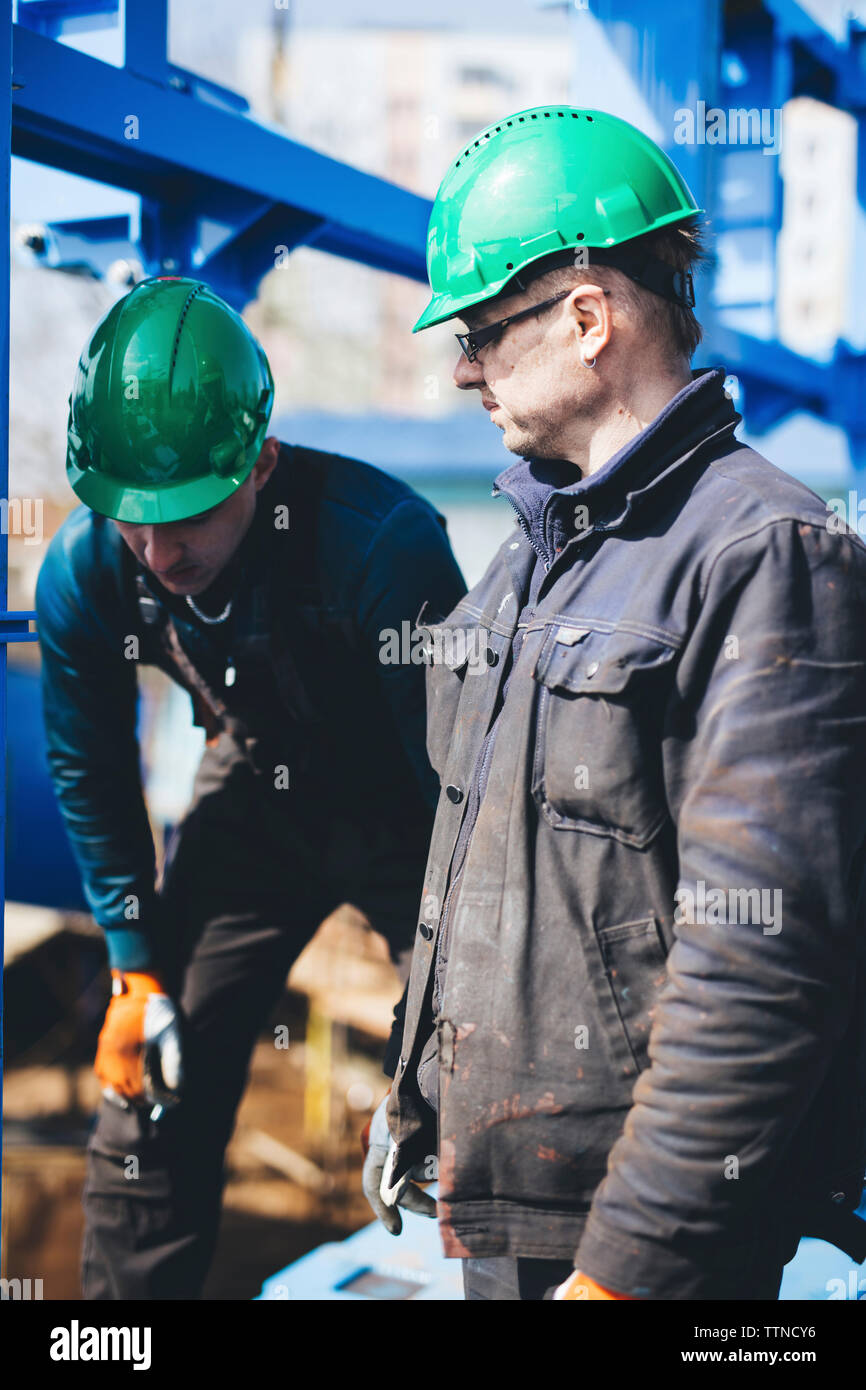 Manual workers wearing hardhats while working together at shipyard - Stock Image