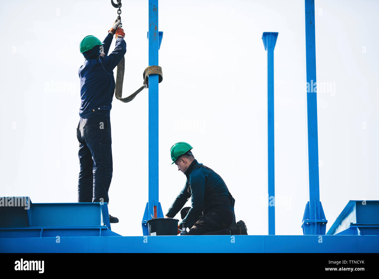 Manual workers working on machinery against clear sky at shipyard - Stock Image