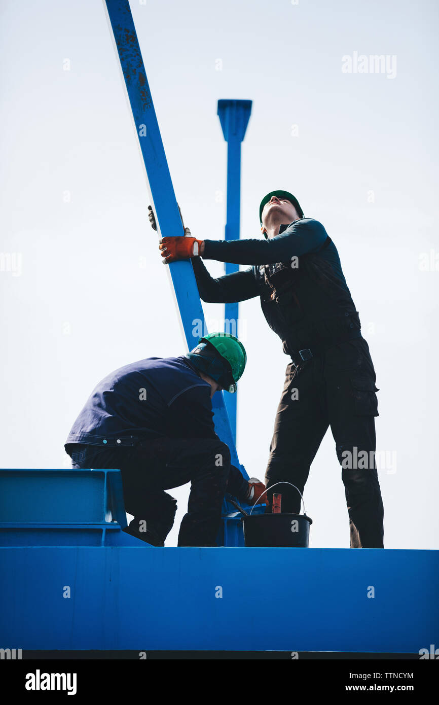 Manual workers working together on machinery against clear sky at shipyard - Stock Image