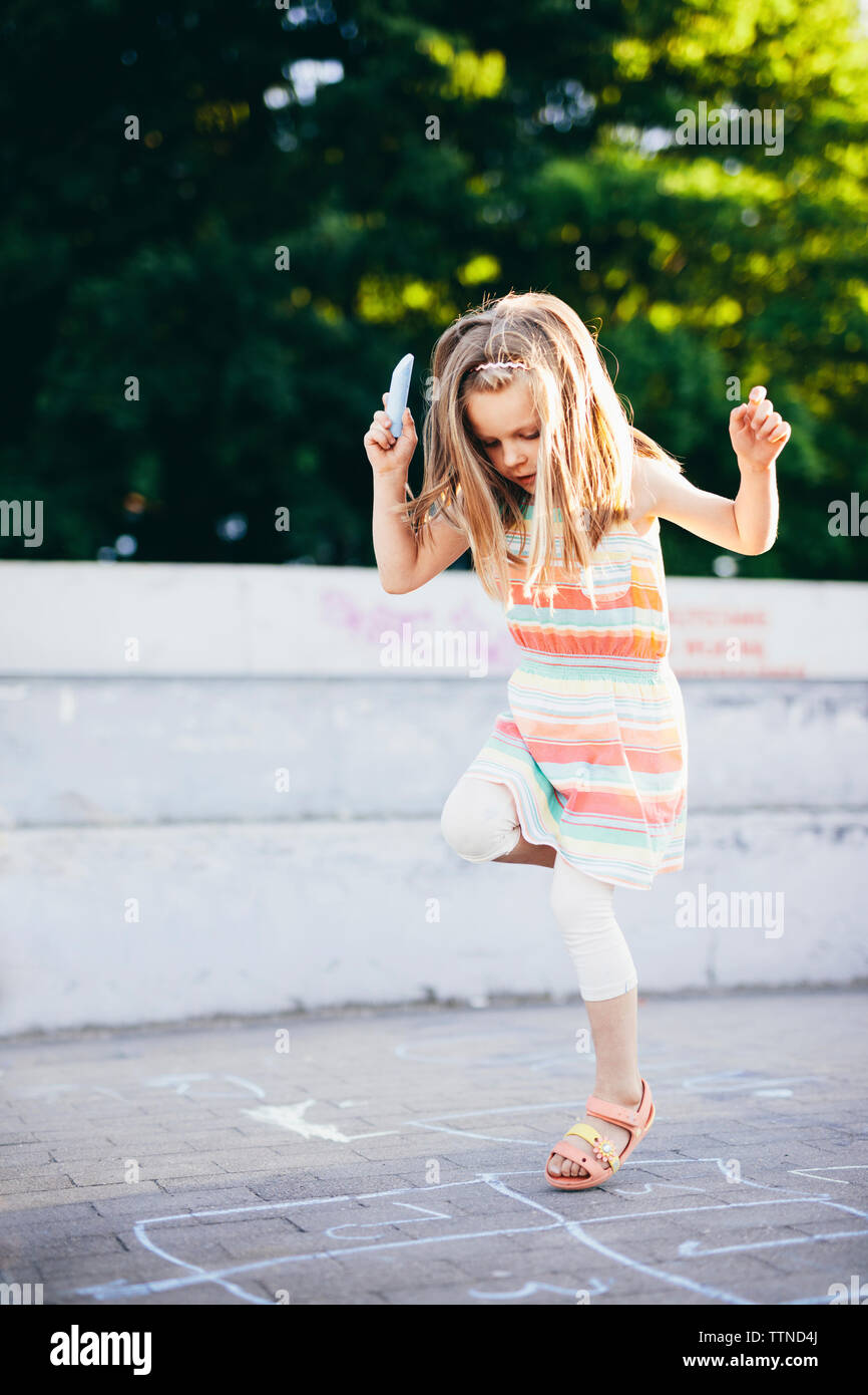 Girl playing hopscotch on street against trees - Stock Image