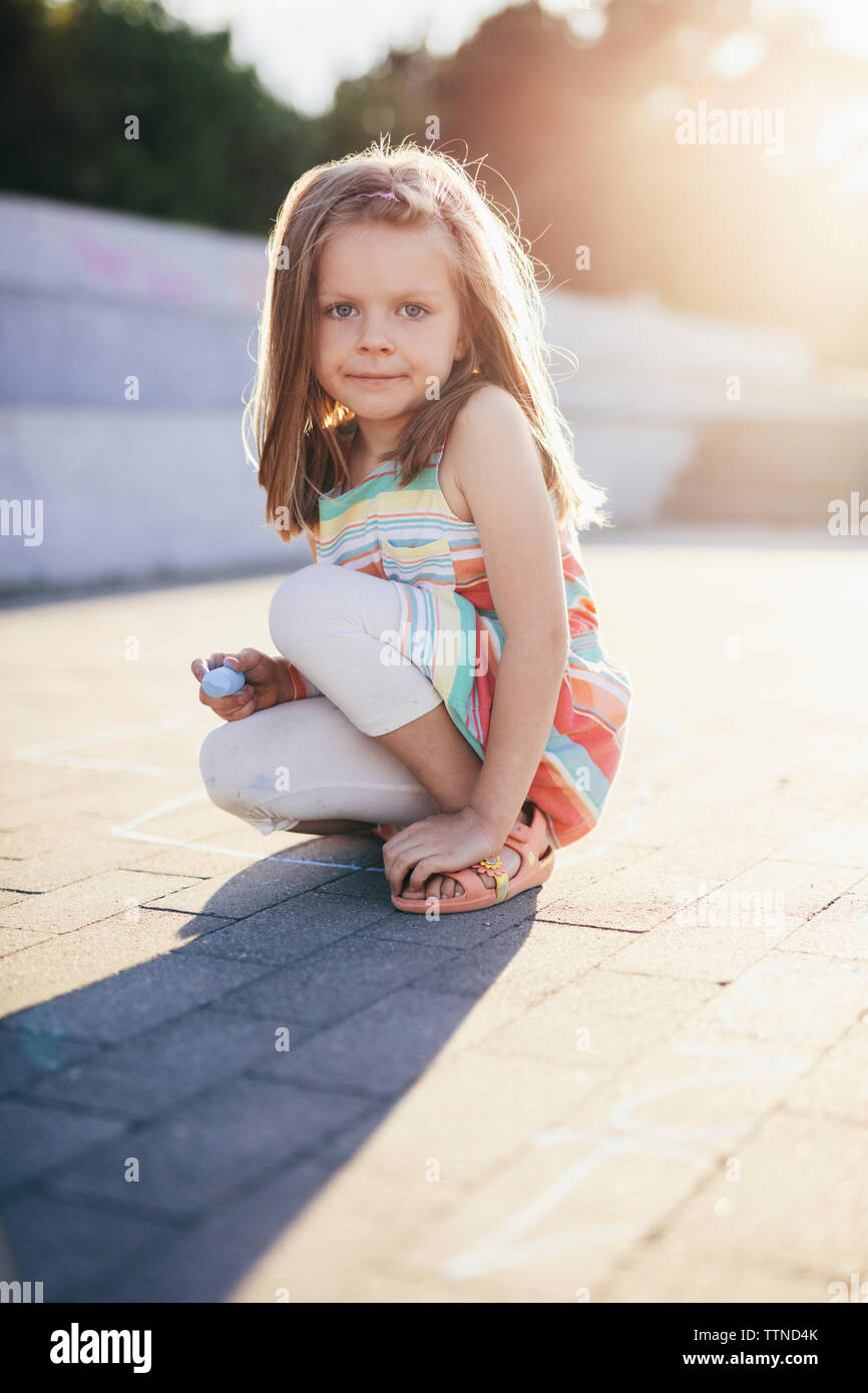 Portrait of girl holding chalk while crouching on street - Stock Image