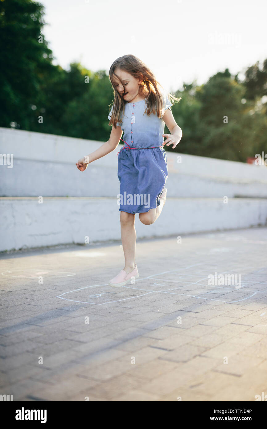 Happy girl playing hopscotch on street against clear sky - Stock Image