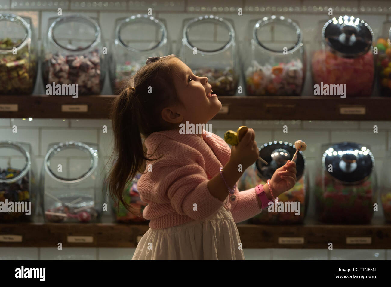 Side view of happy girl holding candies while standing in shop Stock Photo