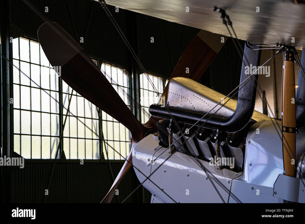 Historic bi-plane silhouette / rim-lit inside a hangar - Stock Image