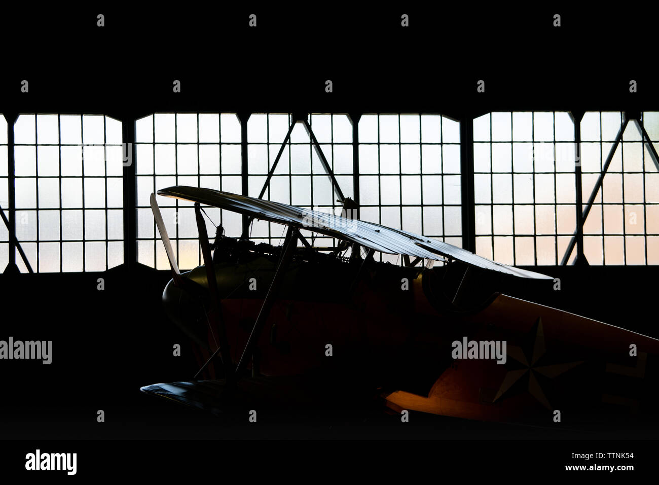 Albatros D.Va replica German Historic WW1 bi-plane silhouette / rim-lit inside a hangar. As flown by the Red Baron, Manfred von Richthofen - Stock Image