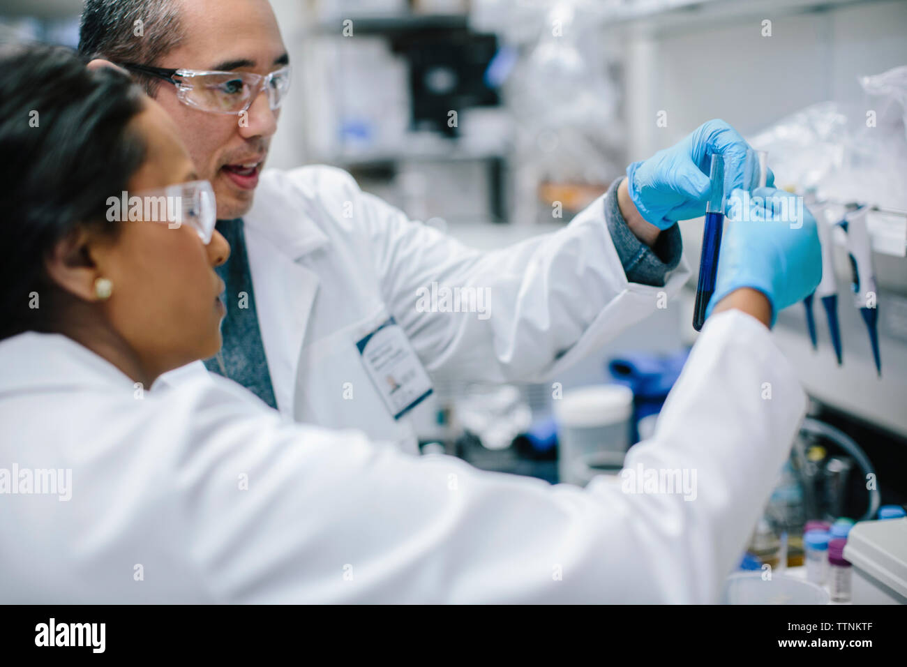 Doctors examining test tubes in laboratory Stock Photo