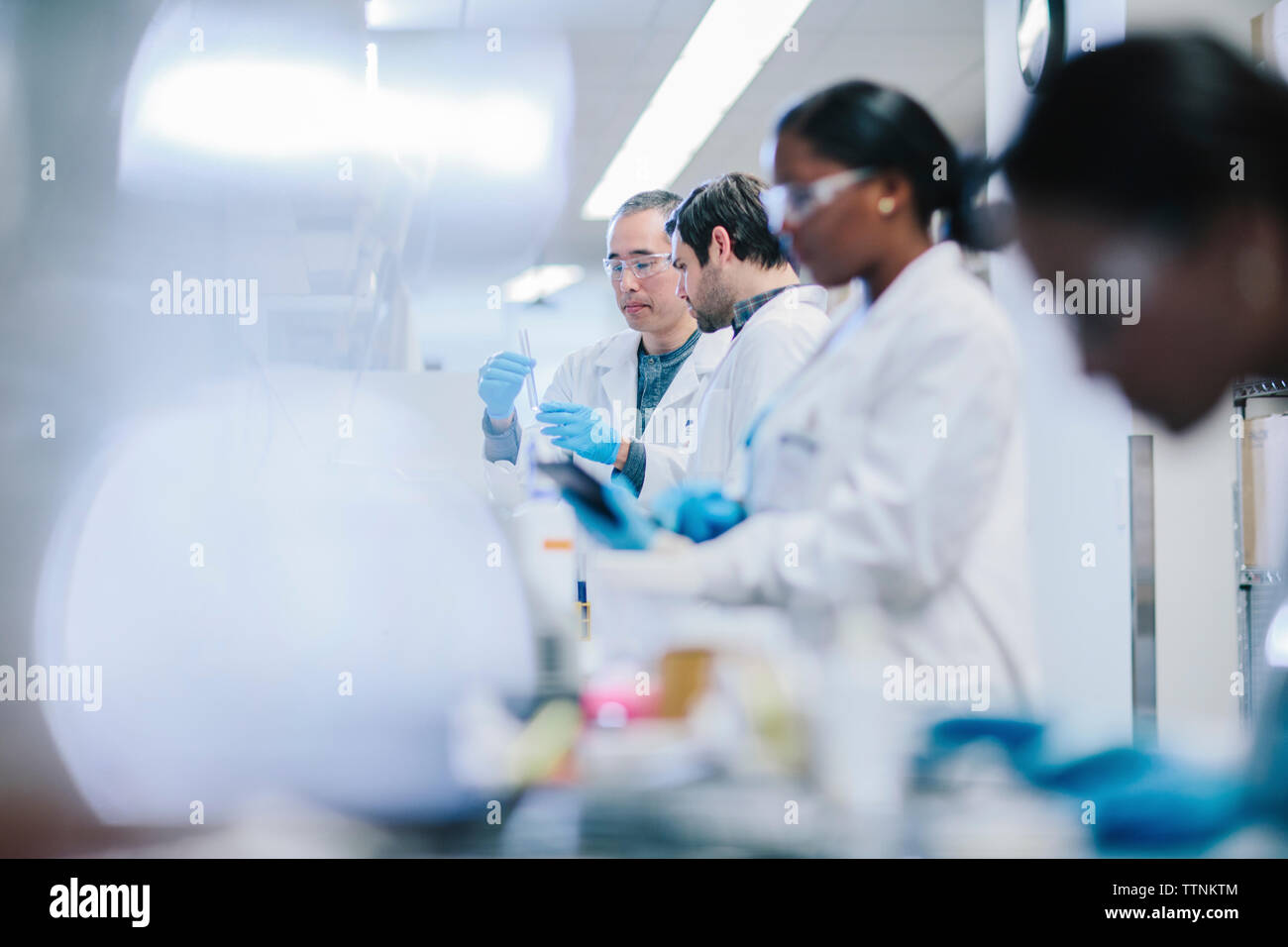 Doctors examining test tubes in laboratory Stock Photo