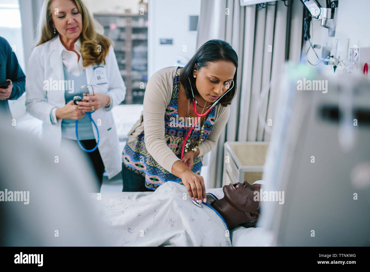 Female doctor training coworkers while examining mannequin in medical school - Stock Image