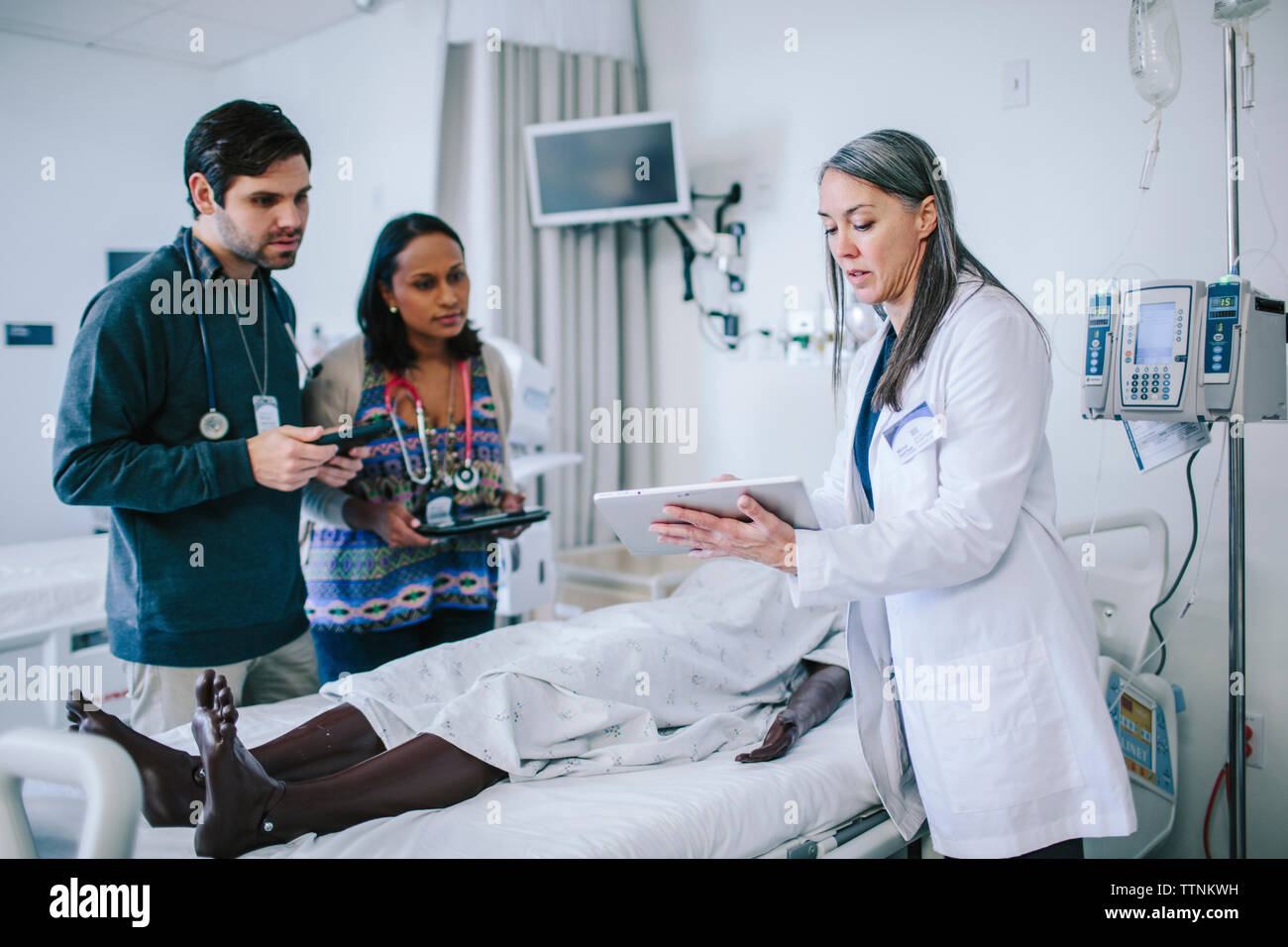 Female doctor training coworkers over tablet computer in medical school - Stock Image