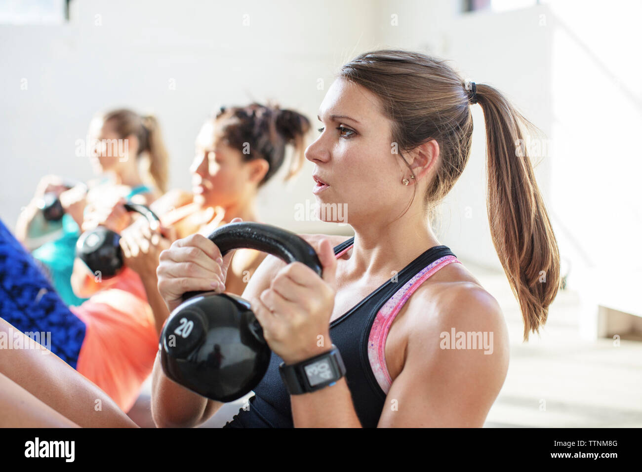 Female athletes lifting kettlebells in gym - Stock Image