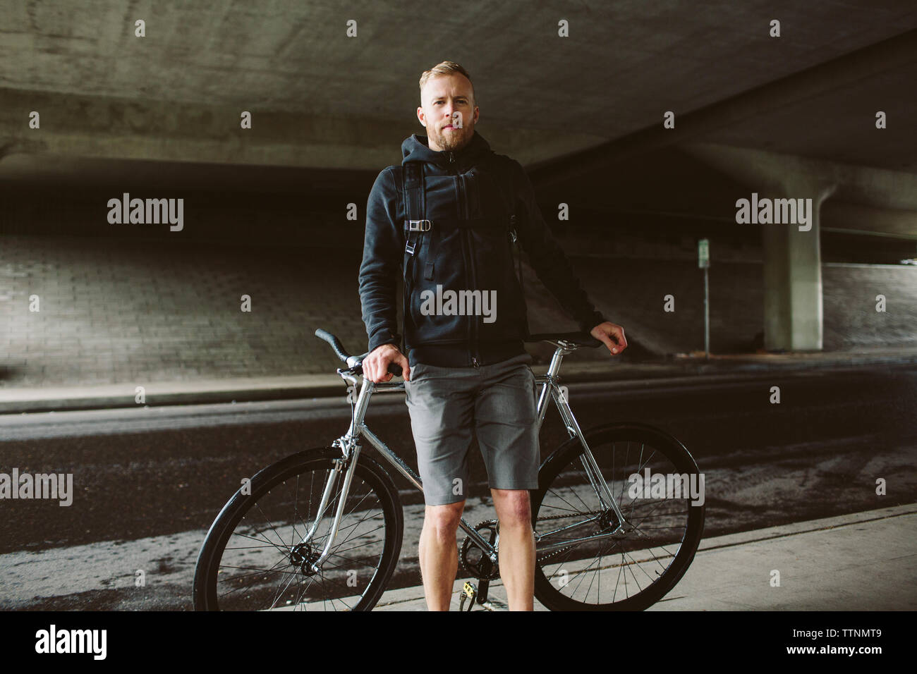 Portrait of confident male commuter standing by bicycle on bridge Stock Photo