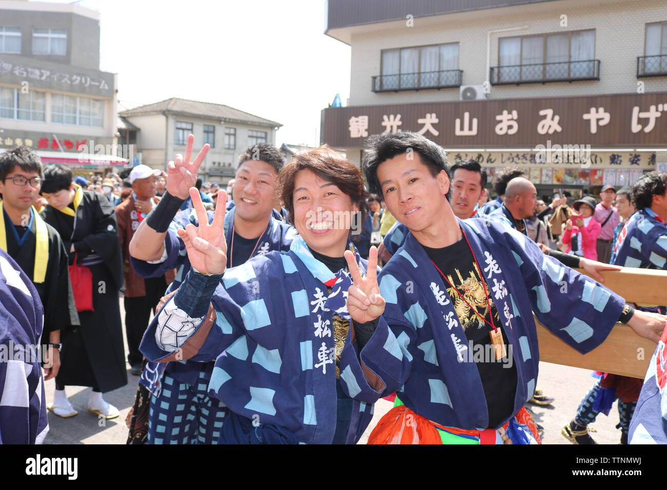 Young men celebrating and laughing after pushing floats in the Inuyama festival showing the two fingered peace gesture Stock Photo