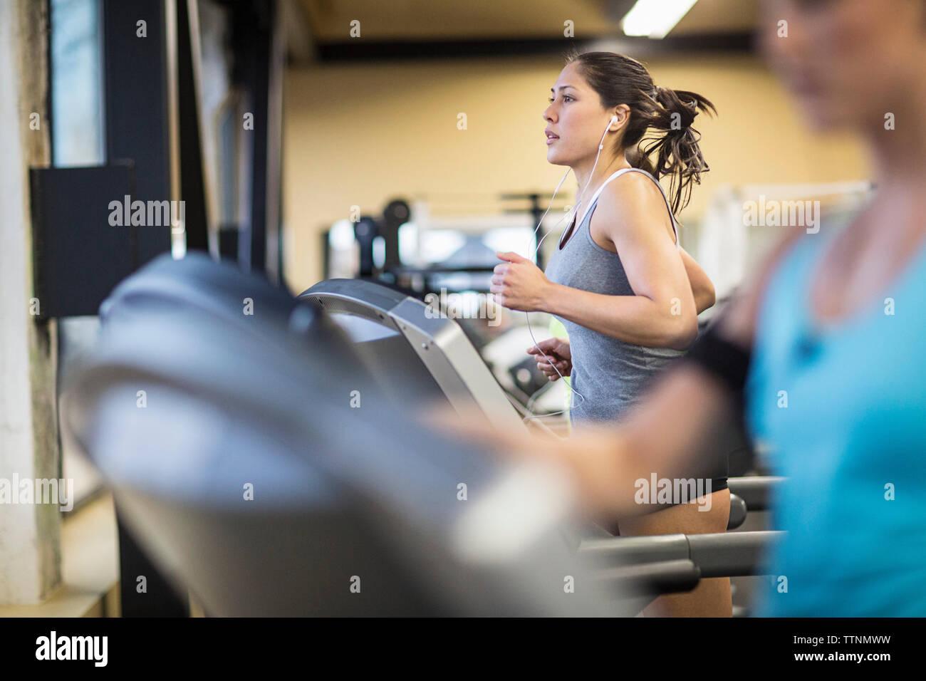 Women exercising on treadmills in health club - Stock Image