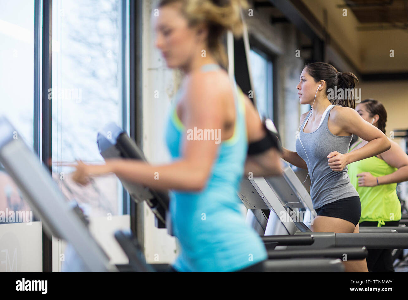 Women listening music while exercising on treadmills in gym - Stock Image