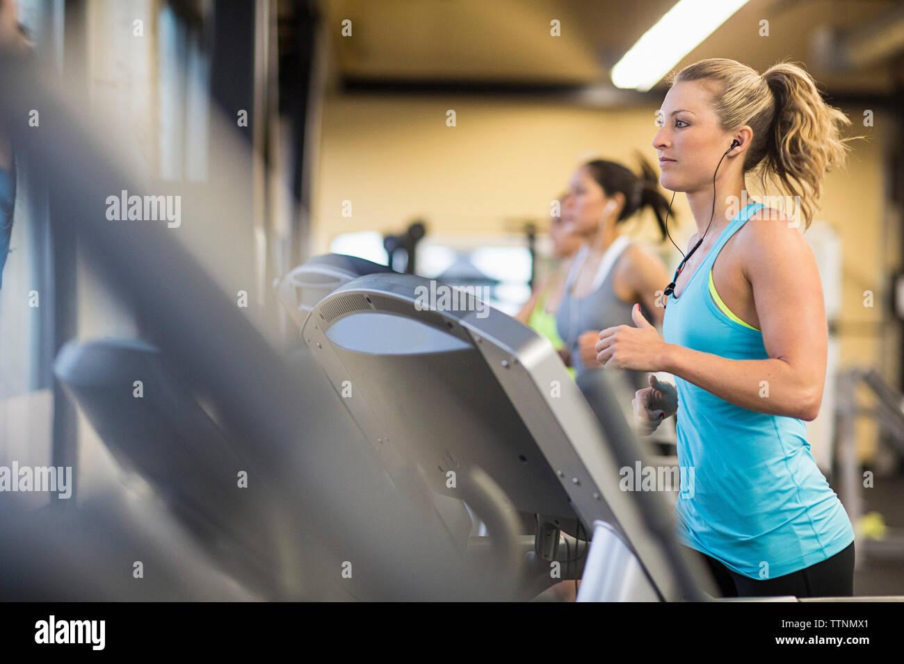 Women exercising on treadmills in gym - Stock Image