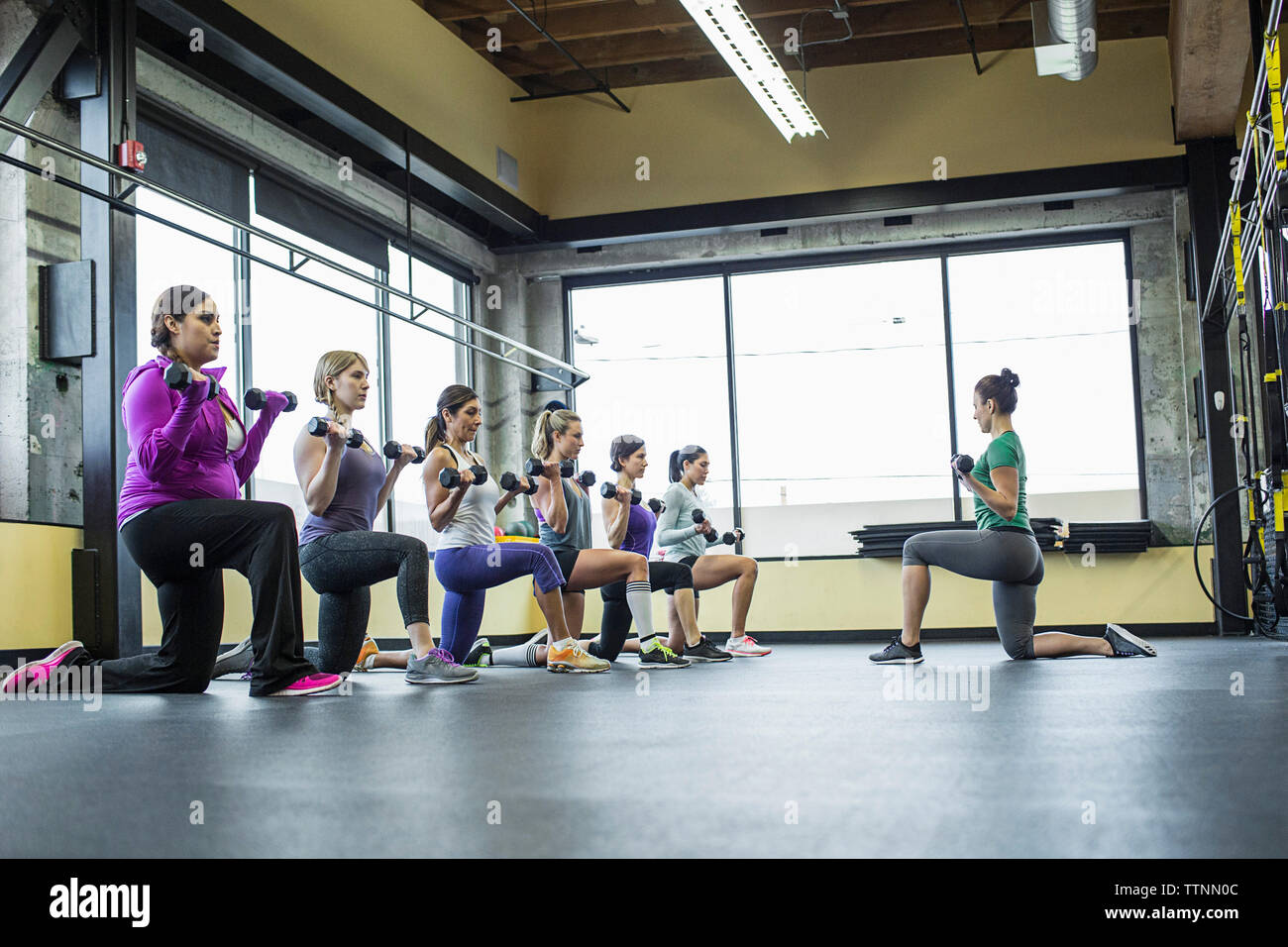 Instructor guiding women in lifting dumbbells at gym - Stock Image