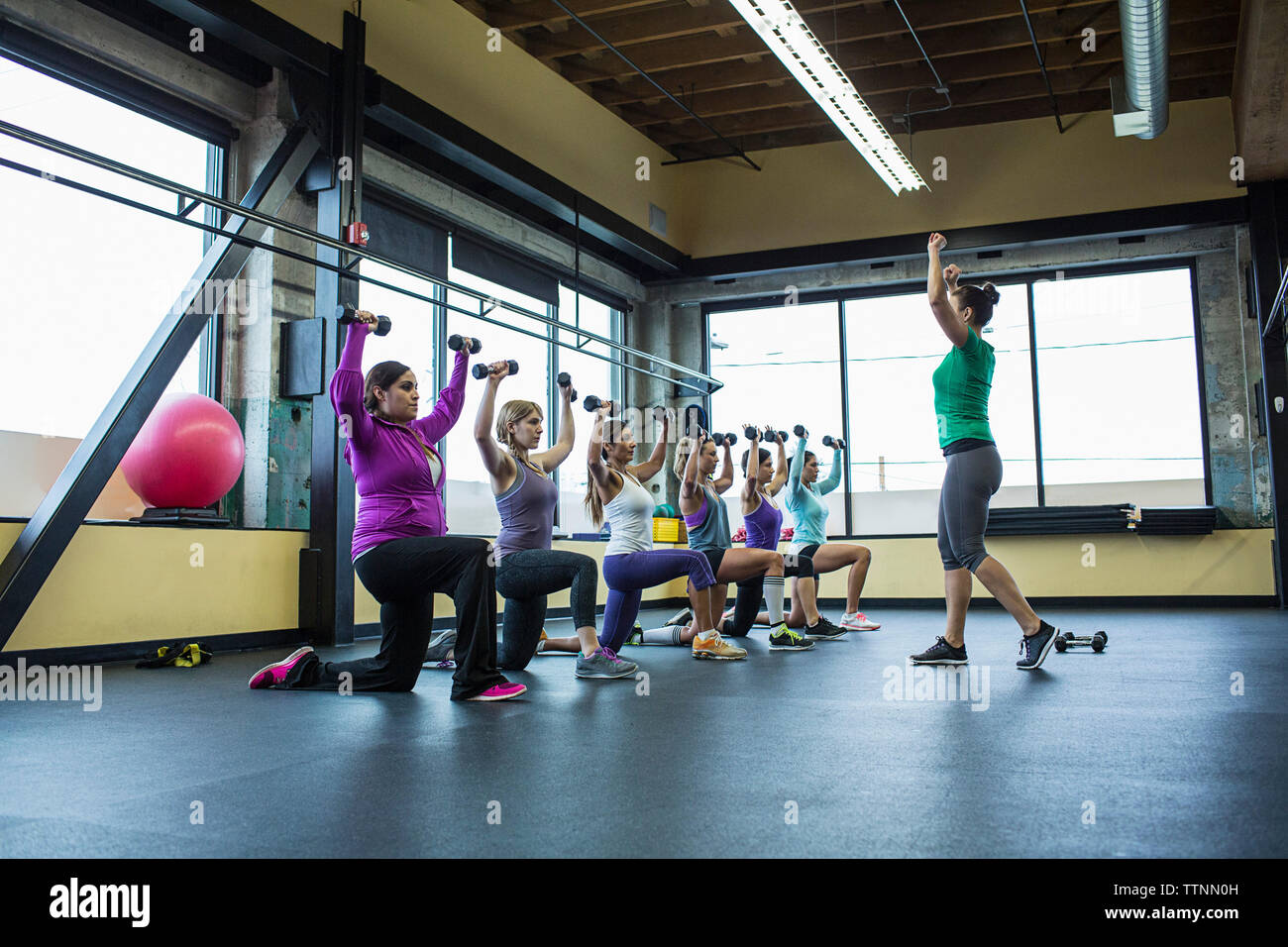 Fitness instructor guiding women in lifting dumbbells at gym - Stock Image