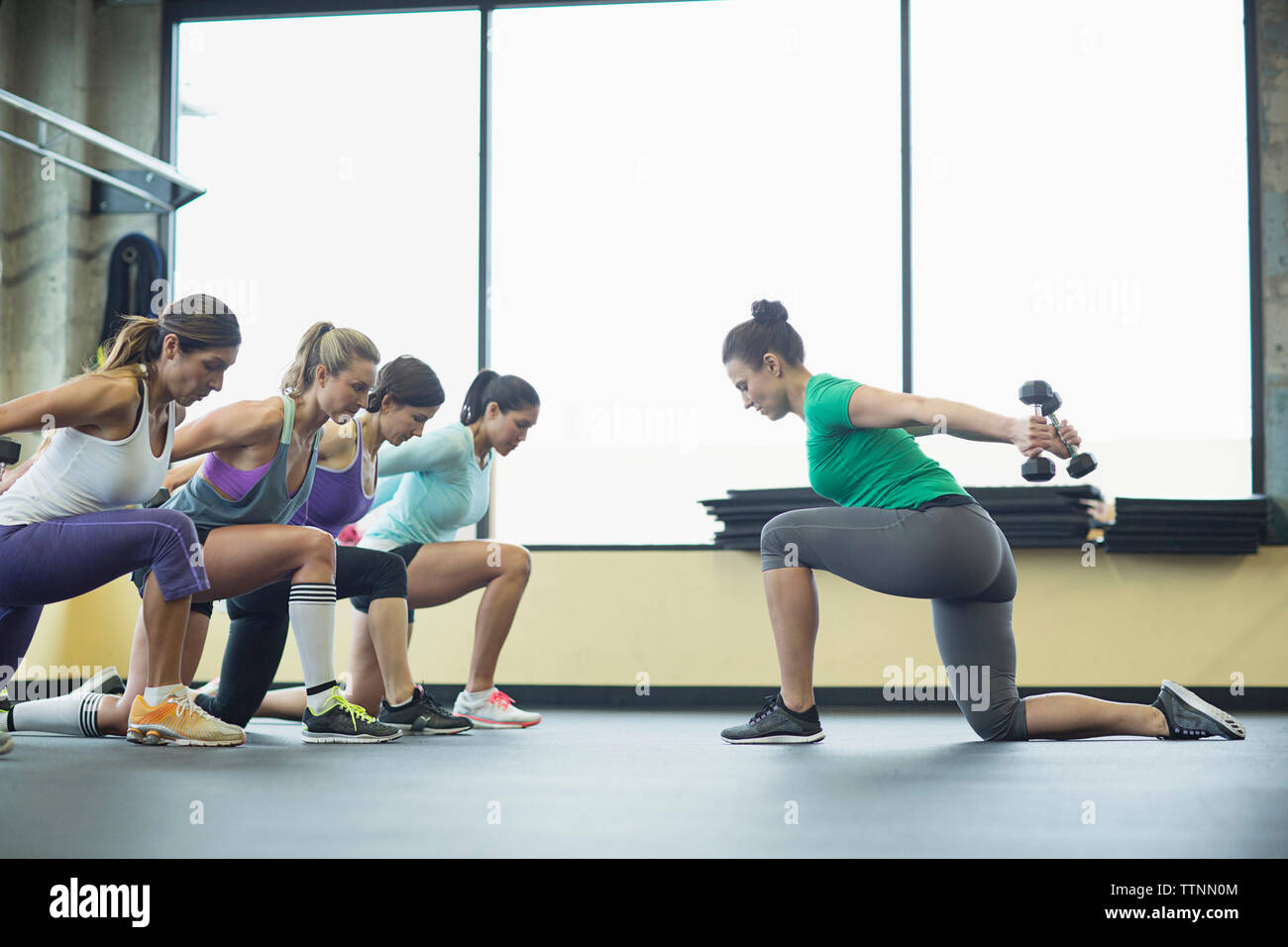 Instructor guiding women in exercising with dumbbells at health club - Stock Image