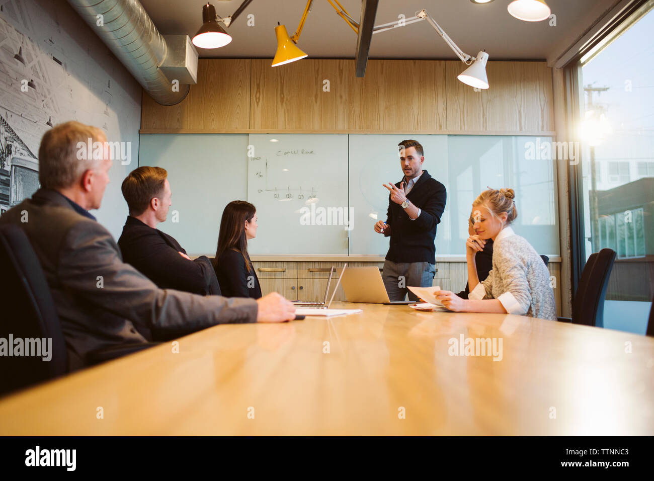 Businessman giving presentation to colleagues in board room - Stock Image