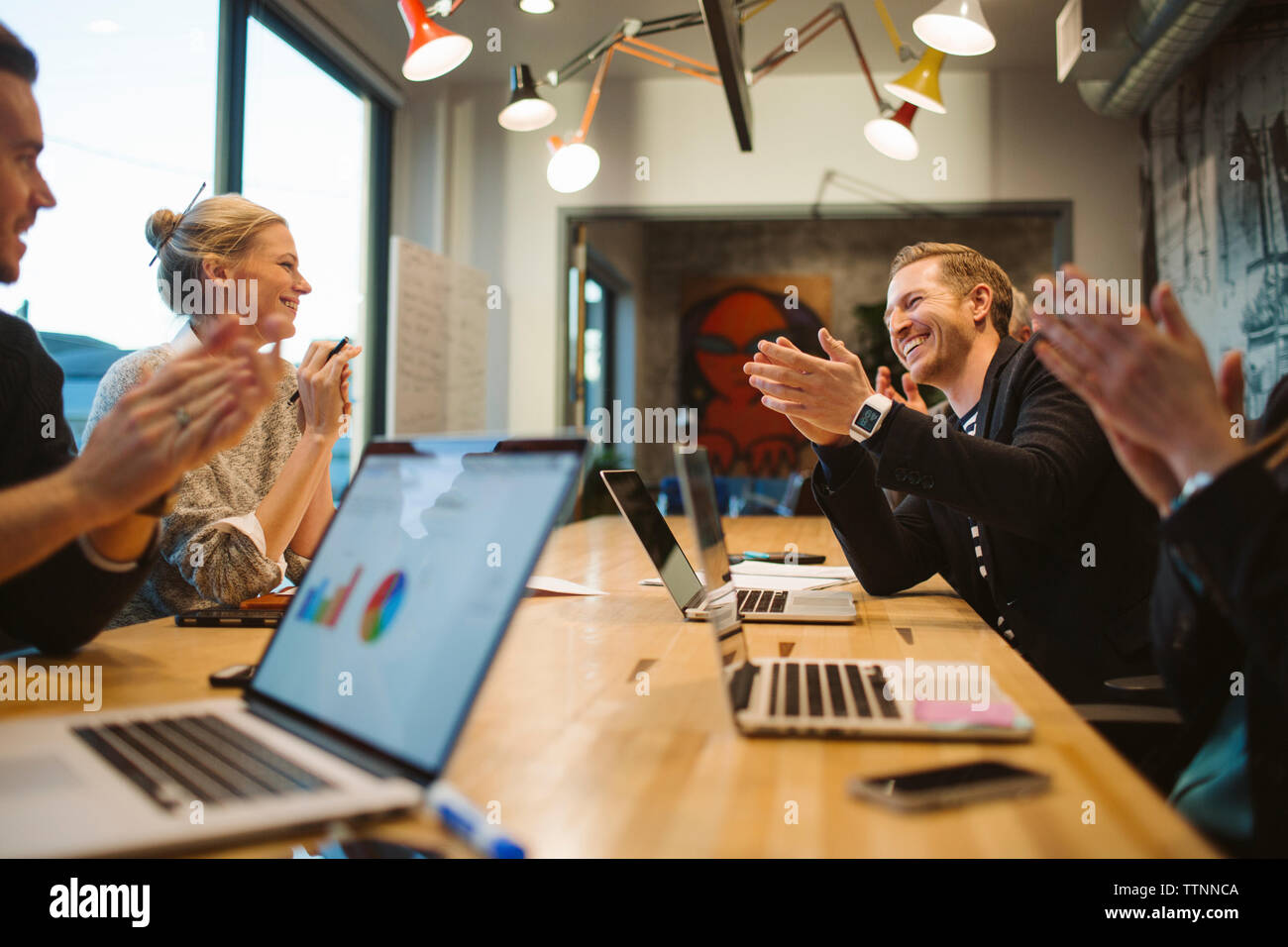 Business people applauding in meeting at board room - Stock Image