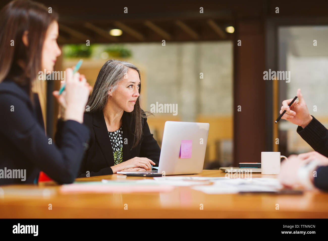 Female colleagues planning in meeting at board room - Stock Image